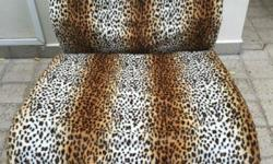A pair of chairs with animal print cover available for