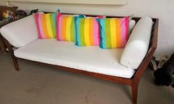 A second hand wooden day bed and matching armchair with