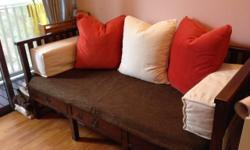 Dark stained daybed made of teak wood with the