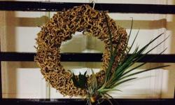 A handmade wreath with two air plants and a mini orchid