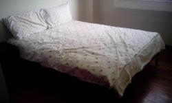 A used solid timber queen bed frame with mattress. In