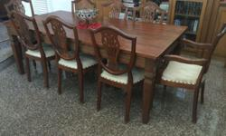 Teak Dining Table with 8 chairs available for sale.