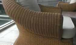 A pair of deep-seat seaters made of wicker and cane