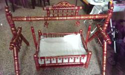 Authentic wooden cradle with ethnic Indian design.